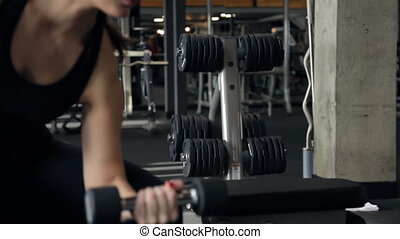 The sportswoman raises and lowers the left hand dumbbell in the gym. Woman performs alternating lifting dumbbells for biceps sitting. Athlete sitting, dumbbell in hand lowered.