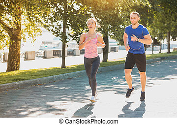 The sporty woman and man jogging at park in sunrise light