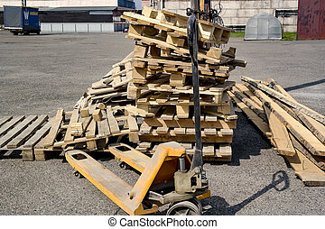 The  stack carelessly folded pallet is folded next to the trolley to carry pallets