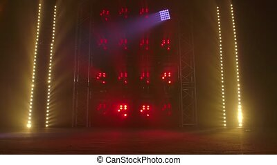 The stage of a small theater with red and yellow spotlights...