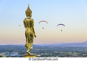 The standing Buddha statue on the twilight sky with the para motor player
