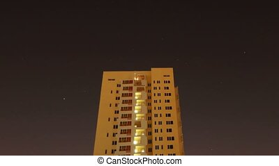 The star sky floats over many-storeyed the house, night. Time Lapse.