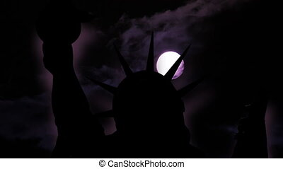 The statue of liberty of New York City against moon at night