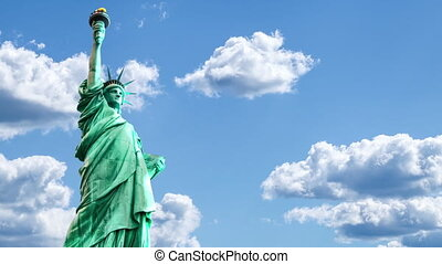 Statue of Liberty with moving clouds in the sky in time lapse. The famous monument symbol of New York City, United States.