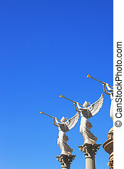 The statues of winged troubadours against the blue sky...