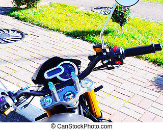 Handlebar of a motorcycle standing on the street on a sunny day