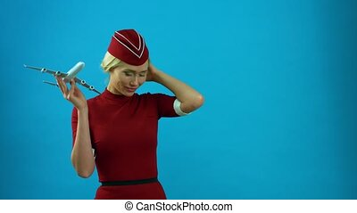 The stewardess smiling with a toy plane in her hands