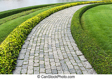The Stone block walk path in the park with green grass...