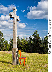 The stone cross and empty wooden chair