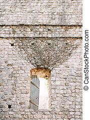 The stone wall of the castle is entwined with dry branches with an oval passage.