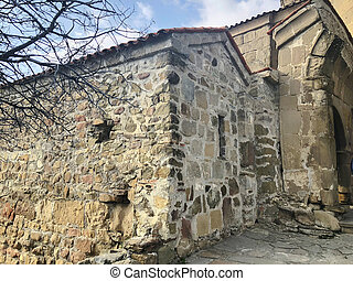The stone wall of the monastery, the road of the lead to the ancient fortress