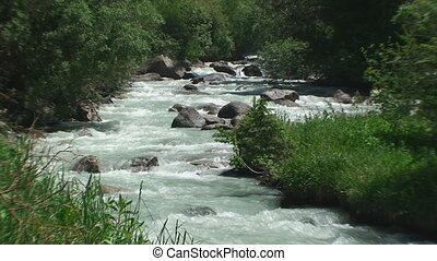 The stony mountain river rages and jumps through stones