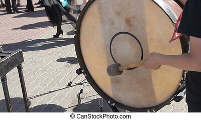 The street drummer is drumming into the drum.