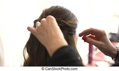 the stylist makes the bride's hair during gathering before wedding ceremony. High quality FullHD footage