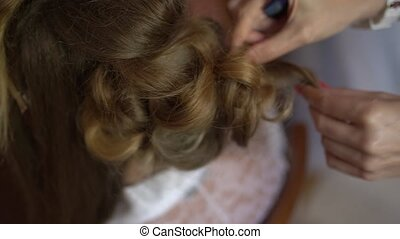 the stylist makes the bride's hair while getting ready before wedding ceremony, close-up. High quality FullHD footage