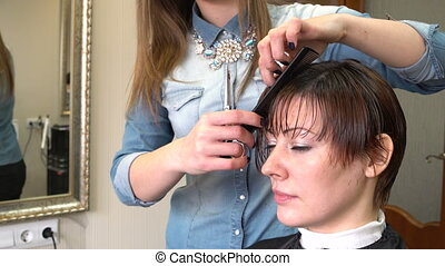 The stylist cuts the hair of a woman with scissors and combs