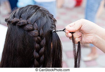 the stylist weaves the female braids on the head
