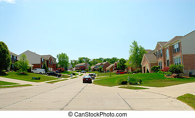 Brick homes line the street in a suburban upscale neighborhood in summer time.