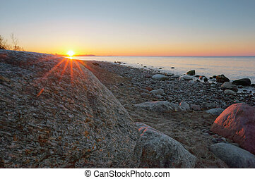 the sun and a large sea boulder, the sun sets over the sea horizon