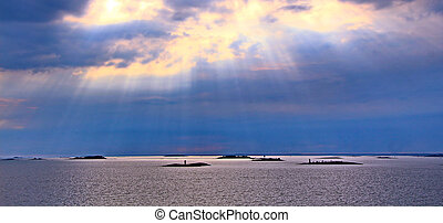 The sun behind the clouds with rays of light shining down on sea