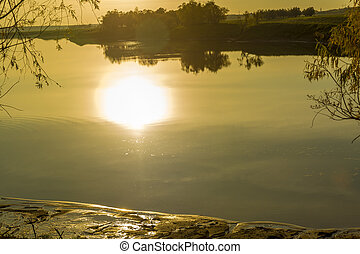 The sun is reflected in the lake before sunset