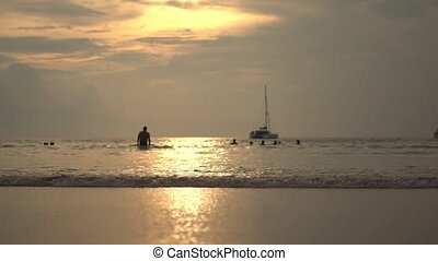 The sun rises over a beautiful beach in Thailand as waves...