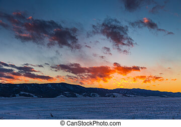 the sun sets behind the mountains and colors the clouds in winter, Altai, Russia