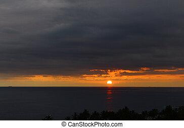The sun sets beyond the horizon