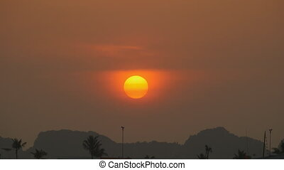 The sun sets in the haze of clouds on the horizon.