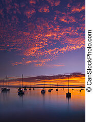 The Sun sets over Poole Harbor in Dorset at Hamworthy pier jetty