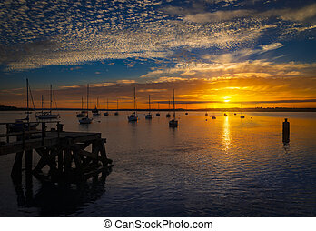 The Sun sets over Poole Harbor in Dorset. Hamworthy pier jetty