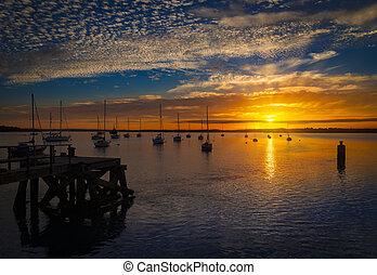 The Sun sets over Poole Harbor in Dorset. Hamworthy pier jetty