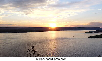 The sun sets over the hills. View of the river at sunset. Time lapse.