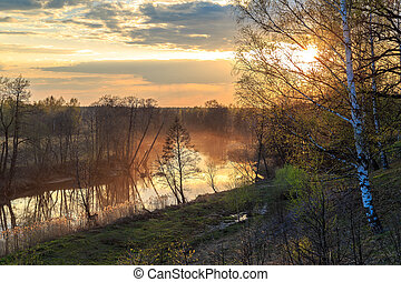 The sun sets over the river