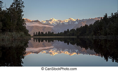 sun setting on mt cook reflected in lake matheson