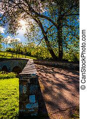 The sun shines through trees over Burnside Bridge, at Antietam National Battlefield, Maryland.