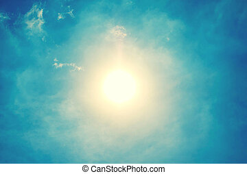 The sun shining brightly against the blue sky background