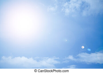 The sun shining brightly against the blue sky