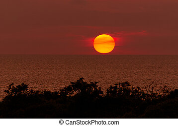 The sun touching horizon line at Koh Sri chang