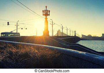 The sun's rays through the street lamp on the bridge in December