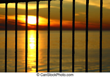 The sunset behind the bars