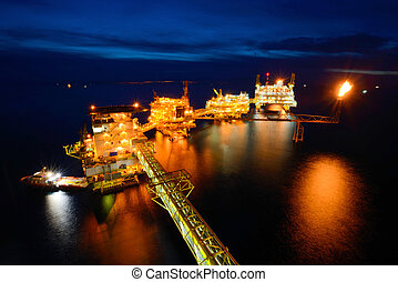 The supply boat is working at large offshore oil rig at night