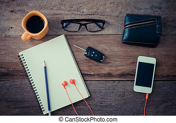 The surface of a wooden table with a notebook, smart-phone, glasses, wallet, car keys, coffee cup