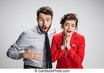 The surprised business man and woman on a gray background -...