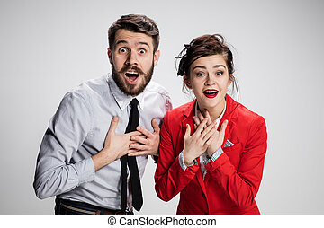 The surprised business man and woman smiling on a gray background