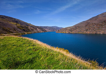 The surroundings of the city of Cromwell among mountains and lakes. Blue sky and light clouds. New Zealand Southern Alps. The concept of ecological, landscape and photo tourism