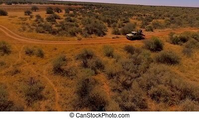 The SUV is driving through the savanna among the wild beasts of Africa.