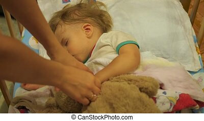 the sweet baby sleeps in a cot with a teddy bear. mother moves a teddy bear