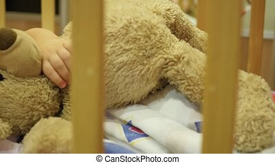 the sweet baby sleeps in a cot with a teddy bear