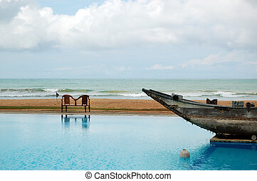 The swimming pool and old traditional boat as decoration in...
